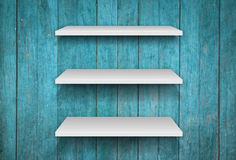 Three white shelves on blue wooden interior texture background Stock Photo