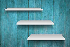 Three white shelves on blue wooden texture background Royalty Free Stock Image