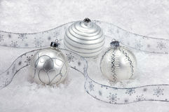 Three white and silver Christmas ornaments on snow Stock Photos