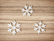 Three white snowflakes on the wooden background, winter decorati Royalty Free Stock Photos
