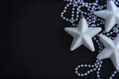 Three white stars and crystalline beads. On the painted black background Royalty Free Stock Image