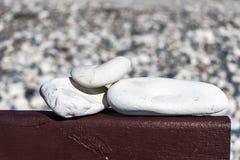 Three white stones on the board Royalty Free Stock Photos