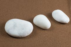 Three White Stones on Brown Sand Stock Images