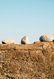 Three white stones on a cement wall with blue sky Royalty Free Stock Photos