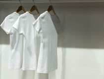 Three White T-Shirts in Wardrobe Royalty Free Stock Image