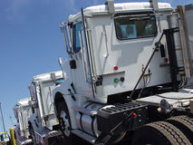 Three White Trucks. A brand new yellow truck transports an additional three new white units royalty free stock photos