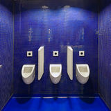 Three white urinals in men public toilet against blue wall. Stock Photo