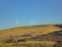 Three White Windmills on Green Field Under Blue Sky royalty free stock image