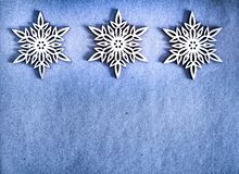 Three White wooden snowflakes on blue craft paper. Three White Wooden Decorative Snowflakes on blue Craft Paper Background, as the Christmas Decor royalty free stock photography