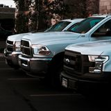 Three white work trucks in a row royalty free stock photo