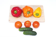 Three whole bell peppers of different colors on the board for cutting in blue bowl for food Royalty Free Stock Image
