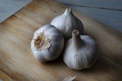 Three Whole Garlic Bulbs on Wooden Chopping Board Stock Image