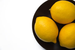 Three whole lemons. Lie on a plate on a white background stock photo