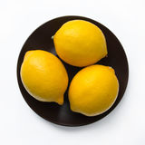 Three whole lemons. Lie on a plate on a white background royalty free stock images
