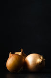 Three Whole Onions on Slate with Black Chalkboard Background Royalty Free Stock Images
