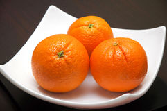 Three whole oranges. On a white plate Stock Images