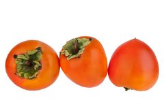 Three whole persimmon orange fruit with green leaves on white background isolated close up, top view, side view, rear view royalty free stock photography