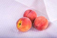 Three whole and red peaches on the white background, close-up. Healthful  fruit. Ingredients for nutritious summer breakfast. Royalty Free Stock Images