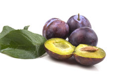 Three whole ripe blue plums two halves Royalty Free Stock Photography