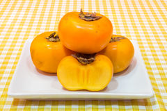 Three whole ripe persimmons and a cross-section of one on ceramic dish Stock Photo