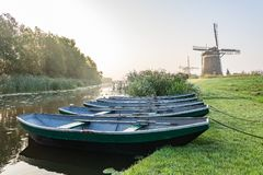 Three wind mills of Molendriegang Leidschendam, Netherlands during a misty Sunrise with five rowing boats in the foreground stock photo