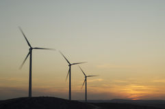Three wind power aerogenerators skyline at dusk royalty free stock images