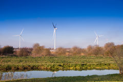 Three Wind turbines blue sky. Three Wind turbines in English countryside  on  blue sky autumn day with canal in foreground Stock Image