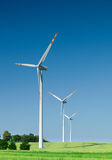 Three wind turbines on green field stock photography