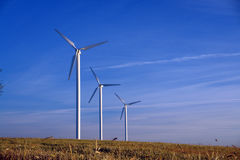Three wind turbines in a row, rural landscape. stock images