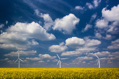 Three Wind Turbines under a blue, cloud-strewn sky Royalty Free Stock Photography