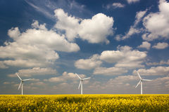 Three Wind Turbines under a blue, cloud-strewn sky Stock Photos