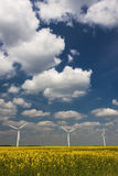 Three Wind Turbines under a blue, cloud-strewn sky Stock Photo
