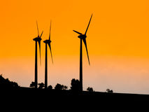 Three wind turbines used for ecological producing electric energy. Sunset silhouettes.  royalty free stock images