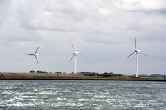 Three windmills. In a row at the shore royalty free stock images