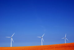 Three windmills in red soil Royalty Free Stock Image