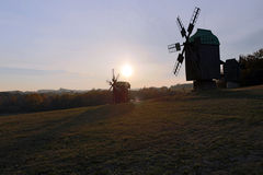 Three windmills on a small hill near the forest on the backgroun Stock Photos
