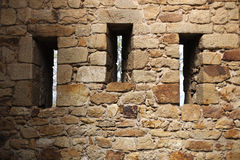 Three window holes on a medieval rock fortress Stock Photos