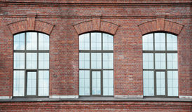 Three window on a red brick wall Stock Photography