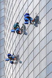 Three window washers. On modern office building Stock Photos