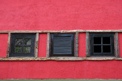 Three window wooden. On red wall Stock Image