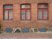 Three windows. With red painted frames in a brick wall, Mecklenburg-Western Pomerania, Germany royalty free stock photo