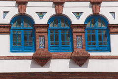 Three windows. Closed blue surrounded by white wall, and bricks Royalty Free Stock Photography