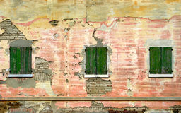 Three windows. Green shutters in a decayed wall Royalty Free Stock Images