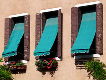 Three windows with awnings in Venice. Three windows with blue-green awnings and flower boxes at a house in Venice Stock Image