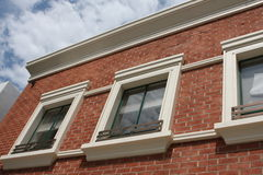 Three windows on brick building royalty free stock photography