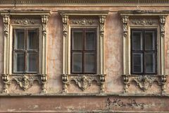 Three windows with carved frames on the facade of the old house royalty free stock photos