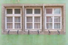 Three windows on classic green old wall in Europe Stock Image