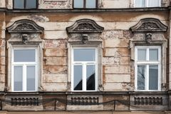 Three Windows on the facade of the old shabby house.  Stock Photo