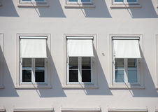 Three windows on grey building with  white awnings and shadow Stock Photo