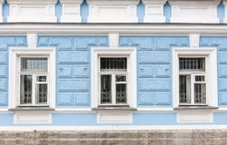 Three windows of the old 19th century mansion with blue walls royalty free stock photography